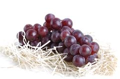 Purple grapes on straw and white Stock Image