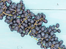 Purple grapes on wooden table Stock Images