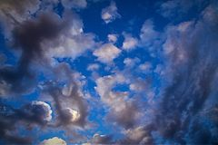 Purple gray Clouds in blue sky. Purplish gray clouds in bright blue sky Stock Photo