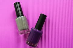 Purple and gray nail polish on a pink background. For nail salon or home use stock photography