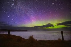 Purple green aurora over the cliff fence stock photography