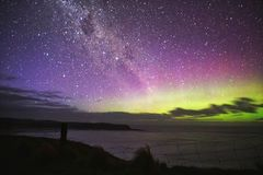 Purple green aurora over the cliff fence stock photo