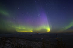 Purple-green-yellowish northern lights in starry sky over hill t Royalty Free Stock Photos