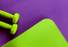 Purple and green yoga mat.. green dumbbells Stock Images
