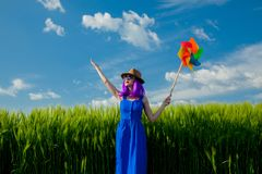 Purple hair girl with pinwheel at wheat field Stock Photos
