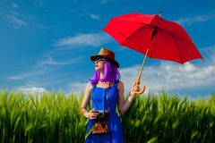 Purple hair girl with umbrella at wheat field Stock Image
