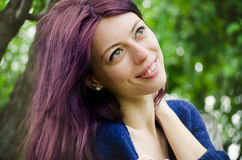 Purple haired girl with a green leafed background. Smiling purple haired girl sitting in front of a green leafed background, with selective focus, enjoying the royalty free stock image
