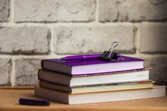 The purple handle rests on a purple diary, a stack of planings, a black clip, a brick background. Notepad for the menu, proper food, the handle is cork-based Royalty Free Stock Photo