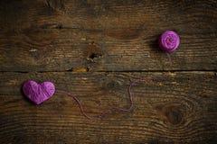 Purple Heart avec une boule de fil dessus sur le vieux backg en bois minable Photo stock