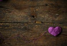 Purple Heart avec une boule de fil dessus sur le vieux backg en bois minable Photographie stock