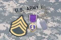 Purple Heart award with dog tags on US ARMY uniform. Purple Heart award with dog tags on US ARMY camouflage uniform Stock Image