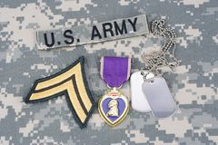 Purple Heart award with dog tags on US ARMY uniform. Purple Heart award with dog tags on US ARMY camouflage uniform Stock Photo
