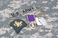 Purple Heart award with dog tags on US ARMY uniform. Purple Heart award with dog tags on US ARMY camouflage uniform Stock Images