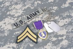 Purple Heart award with dog tags on US ARMY uniform. Purple Heart award with dog tags on US ARMY camouflage uniform Royalty Free Stock Photography