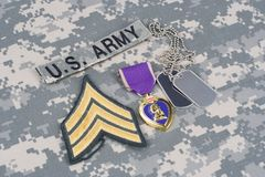 Purple Heart award with dog tags on US ARMY uniform. Purple Heart award with dog tags on US ARMY camouflage uniform Royalty Free Stock Images