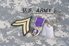 Purple Heart award with dog tags on US ARMY uniform. Purple Heart award with dog tags on US ARMY camouflage uniform Royalty Free Stock Photos