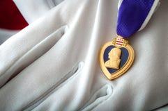Purple Heart medalj som rymms med vita handskar Fotografering för Bildbyråer