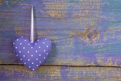 Purple heart shape on purple wooden surface - love and hope, gre Royalty Free Stock Photography