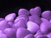 Purple Hearts. Purple candy hearts piled high against black background Royalty Free Stock Image