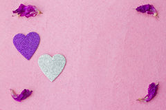 Purple hearts and flower petals Stock Photos