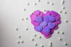 Purple hearts and pearls lying on a beige fabric stock images