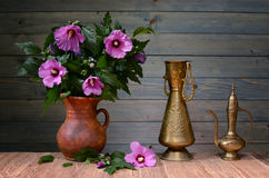 Purple hibiscus in a ceramic vase. On the table Royalty Free Stock Images