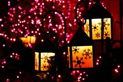 Purple holiday decorations. Christmas decorations in the form of purple and yellow lights and lanterns showing snowflakes in silhouette Royalty Free Stock Photo