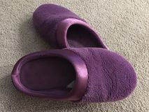 Purple house slippers left on the floor. Royalty Free Stock Photo