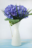 Purple hydrangea in white vase. On turquoise wooden board Royalty Free Stock Images