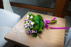 Purple irises bouquet over wooden table Royalty Free Stock Images