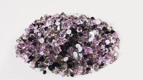 Purple jewel stones heap turning over white, loop ready stock video