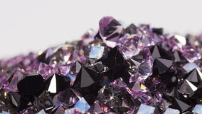 Purple jewel stones heap turning over white, loop ready stock footage