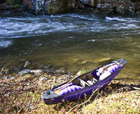 Purple Kayak on the River Bank. A purple kayak on the bank after a run down the river Royalty Free Stock Image