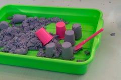 Kinetic sand and pink mini plastic bucket. Purple kinetic sand and pink mini plastic bucket royalty free stock photo