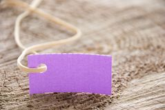 Purple label on wood. A purple label tag with copy space on a trunk of wood Royalty Free Stock Images
