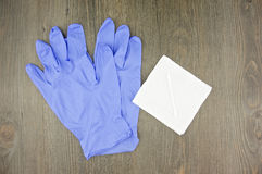 Purple latex gloves and cotton bud on tissue paper Royalty Free Stock Photos
