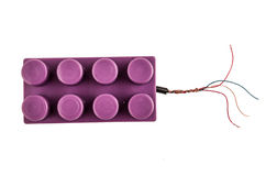 Purple lego brick connected to open wires Royalty Free Stock Images