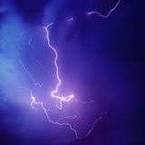 Purple Lightning Bolt. Beautiful natural lightning bolt in a dark blue purple sky during a thunder storm stock photography