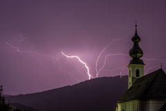 Purple lightning storm with church in foreground Stock Photography