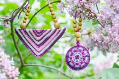 Purple lilac bush and crochet handmade accessories. Purple lilac bush an crochet handmade accessories. Handicraft manufacturing. Spring branch of blossoming royalty free stock image