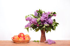 The purple lilac in a ceramic vase and apples Royalty Free Stock Photography
