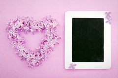Purple lilac flower heart with an empty blackboard Royalty Free Stock Photography