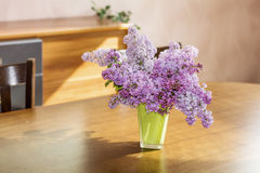 Purple lilac  in a green glass vase on a wooden table Royalty Free Stock Images