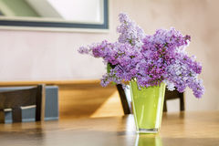 Purple lilac  in a green glass vase on a wooden table Royalty Free Stock Photo