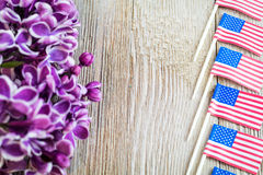 Purple lilac and miniature flags focused on wooden board with room for copy Stock Photo