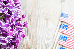 Purple lilac and miniature flags on wooden board with room for copy Royalty Free Stock Images