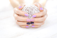 Purple manicure with a white ball of yarn Royalty Free Stock Photography