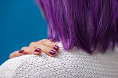 Purple manicured fingers with a girl with purple hair stock photography