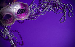 Purple Mardi-Gras or Venetian mask on purple background royalty free stock photo