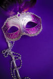 Purple Mardi-Gras or Venetian mask on purple background Royalty Free Stock Image